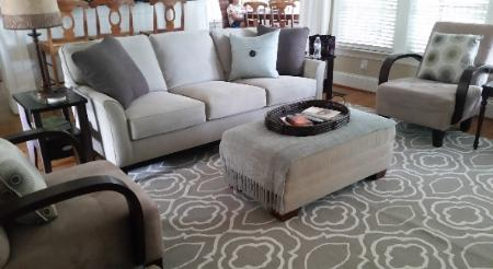 Contemporary living room with gray Broyhill sofa, geometric rug, and oversized ottoman Cary NC Red Chair Home Interiors