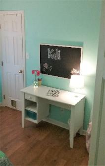 Girls bedroom with white desk, chalkboard cork board, and Teal Zeal paint