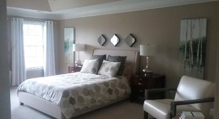 Sophisticated bedroom in Cary, NC paint is Balanced Beige by Sherwin Williams Red Chair Home Interiors