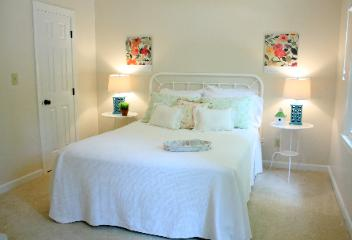 Staged bedroom in Cary NC with white matelasse bedspread and Kim Parker prints by Red Chair Home Interiors