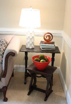 Eclectic vignette with white lamp from Home Goods, red bowl with moss balls, and nesting tables Red Chair Home Interiors, Cary, NC