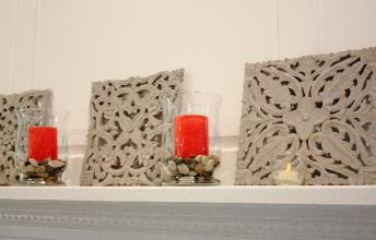 Eclectic mantel in Cary, NC  featuring gray carvings and red candles on river rocks in glass hurricaines