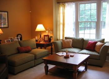 Redesigned living room featuring fall color pallete Red Chair Home Interiors