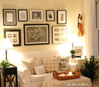 Cottage farmhouse style living room with Sherwin Williams Rice Grain paint, black and white gallery wall and hanging violin by Red Chair Home Interiors Cary, NC