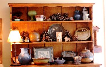 Mountain style shelves staged with pinecones and pottery Cary NC