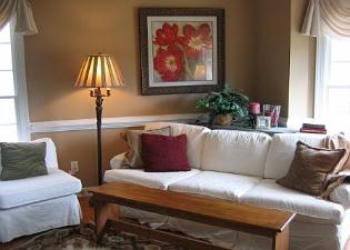 Apex living room with white slipcovered sofa, bench as coffee table, large scale floral art, bay window Red Chair Home Interiors