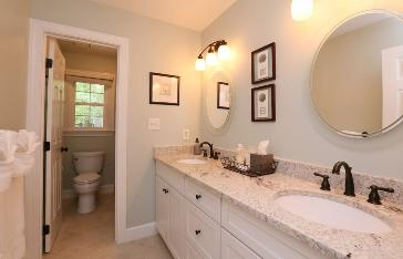 Cottage farmhouse style bathroom in Cary, NC.  White cabinets. Walls Sherwin Williams Comfort Gray FIxtures oil rubbed bronze Red Chair Home Interiors