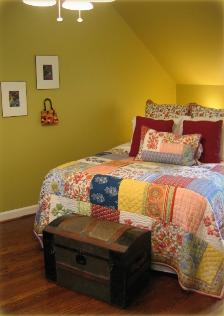 Cary NC bedroom with Pottery Barn quilt and collage art on walls Paint is Timothy Straw by Benjamin Moore