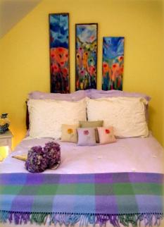 Cary NC guest bedroom featuring yellow walls, purple bedding, and original barn art paintings