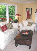 Cary NC living room with Benjamin Moore Straw walls, Z Gallerie art, and white slipcovered sofa