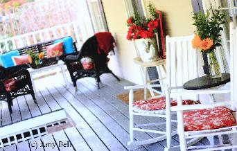 Covered porch with white rockers rocking chairs, black porch swing, black wicker chairs, sunflowers, and red and white toile cushions Photo by Red Chair Home Interiors Cary NC
