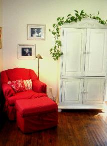 Red chair and ottoman with armoire in living room