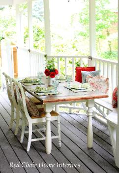 Farmhouse covered porch dining area with reclaimed table and built in bench Cary NC Red Chair Home Interiors